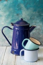 Enameled Blue Tea Pot And Mugs On Table