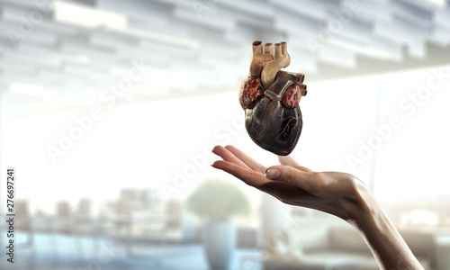 Fotobehang Hoogte schaal Woman`s hand showing anatomical heart model. Mixed media.