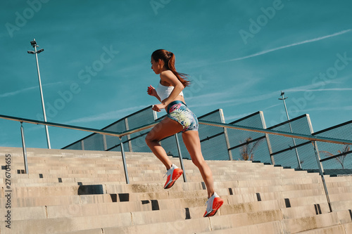 plakat Training to become the best. Full length of beautiful young woman in sports clothing running while exercising outdoors