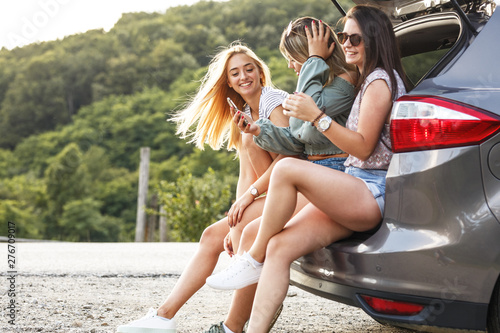 Poster Affiche vintage Group of female best friends on travel . They sitting on car trunk and relaxing after long journey.
