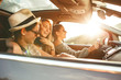 canvas print picture - Three best female friends travel together.They drives a car and making fun.Sunset.