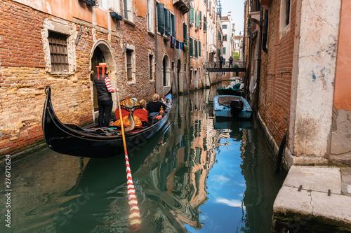 Fotografía  Venetian gondolier punts gondola through narrow canal waters of Venice, Italy