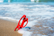 Red Eyeglasses On The Sand Of A Beach