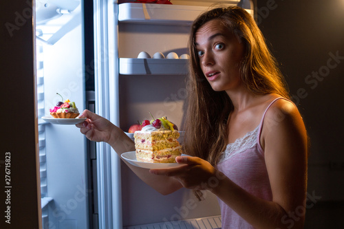 Cuadros en Lienzo Hungry surprised woman in pajamas eating sweet cakes at night near fridge and gain extra pounds because of high carbs food and unhealthy night eating