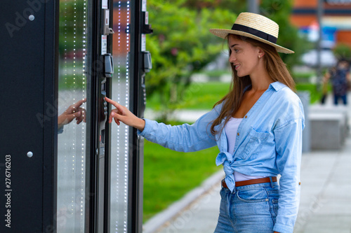 Obraz Young woman in hat using vending machine on the street during a walk in the city park for buying soda and sweets - fototapety do salonu