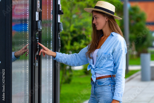 Obraz Young woman in hat buying soda, water and sweets in vending machine on the street during a walk in the city park - fototapety do salonu