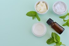 Natural Homemade Lip Balm With Shea Butter, Coconut Oil And Peppermint Essential Oil, Top View On Green Background.