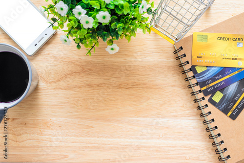 Fototapeta Credit cards,notebook,flower pot tree,smartphone,Shopping cart and coffee cup on wooden background,Online banking Concept,Top view office table. obraz na płótnie