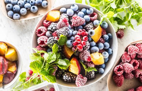 Obraz Frozen fruits blueberries blackberry raspberry red currant peach and herbs melissa - fototapety do salonu