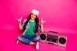 Leinwandbild Motiv Full length body size photo beautiful little small she her curly lady crazy enjoy metal sound sit old tape audio recorder legs crossed wear specs hat casual jeans denim jacket isolated pink background