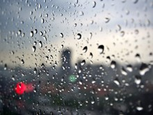 Rain Drops On The Glass With Blur Cityscape And The Bokeh Light