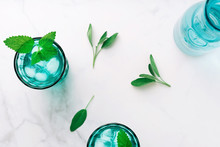 Top View Of Two Beautiful Vintage Turquoise Glasses And A Bottle With Cold Drink And Ice Cubes, Decorated With Fresh Green Mint Leaves On White Marble Table. Copy Space.