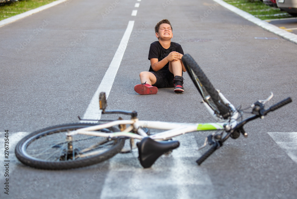Fototapety, obrazy: Kid hurts his leg after falling off his bicycle. Child is learning to ride a bike. Boy in the street ground with a knee injury screaming after falling off to his bicycle.
