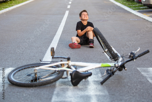 plakat Kid hurts his leg after falling off his bicycle. Child is learning to ride a bike. Boy in the street ground with a knee injury screaming after falling off to his bicycle.