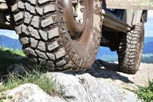 Close-up Detail - Dirty Tyre Of An Off-road SUV 4x4 Stopped On A Rock High In The Mountain