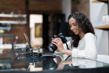 Female Photographer Sitting On The Desk With Laptop At Home
