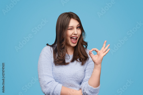 Cheerful plump woman winking and gesturing OK Wallpaper Mural