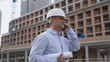 Architect or engineer at work on a building site. Holding plans for construction work. Confident gaze and smile at camera. Using telephone. 4K