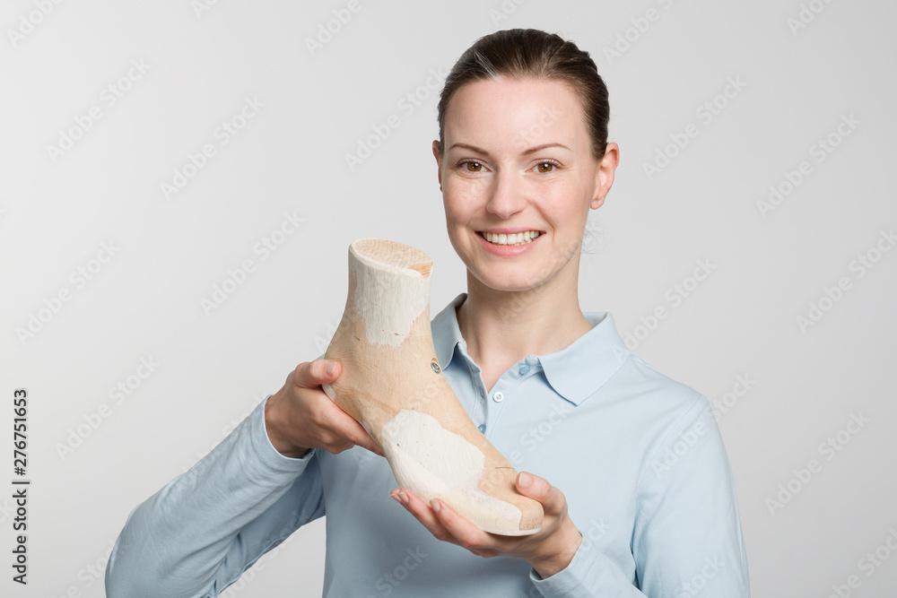 Fototapety, obrazy: Female orthopedic shoemaker shows a handmade wooden last