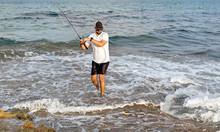 Fisherman Standing At The Seashore Hooks A Fish.
