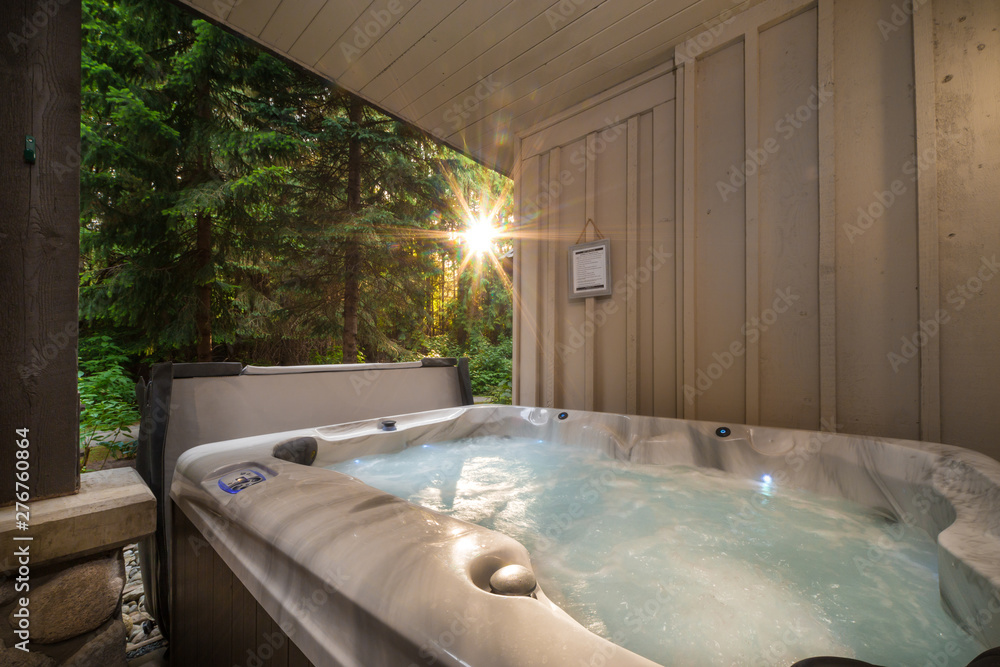 Fototapeta A outdoor hot tub near a forest with a sunburst coming through the trees.
