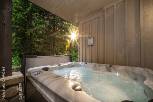 Foto A outdoor hot tub near a forest with a sunburst coming through the trees