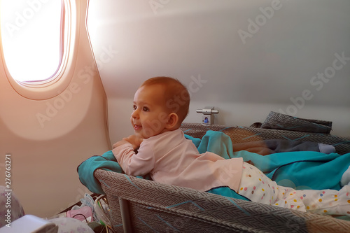 Photo Happy infant baby lyes in special bassinet in airplane at his stomach