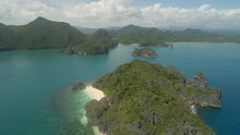 Aerial View Of Islands With Sand Beach And Turquoise Water In Blue Lagoon Among Coral Reefs, Caramoan Islands, Philippines. Mountains Covered With Tropical Forest.