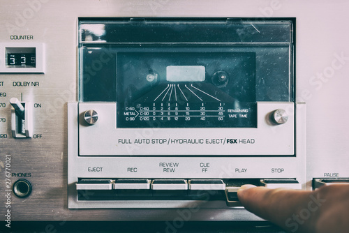 A finger presses the button of the game cassette player - 276770021