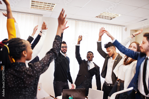 Fototapeta Multiracial business people standing at office and put hands up. Diverse group of employees in formal wear. obraz na płótnie