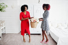Two Fashionable African American Woman In Evening Dress Standing With Flowers Basket On Hands Against Old Vintage Wardrobe At White Room.