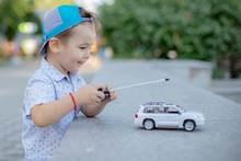 A Boy Playing With A Car Remote.a Small Child Playing In The Park With A Toy Car White Controls It Remotely