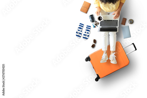 Obraz Tourist concept, a girl with a laptop put her feet on the suitcase - fototapety do salonu
