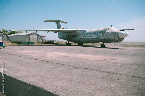 abandoned military aircraft on an empty airfield near the hangar against the blue sky Wallpaper Mural