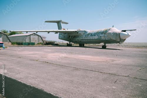 Photo abandoned military aircraft on an empty airfield near the hangar against the blue sky