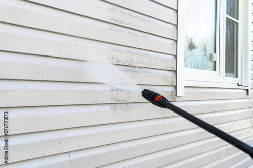Photo Cleaning service washing building facade with pressure water