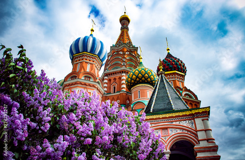 Obraz Spring in Moscow Red Square. A vibrant purple lilac tree blossom and a famous Saint Basil's Cathedral with blue cloudy sky at the backround.  - fototapety do salonu