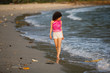 Asian woman walks along a polluted tropical beach. Pollution and environmental problems.