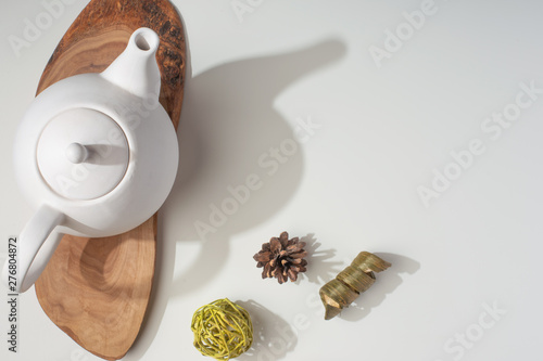 Fotografie, Obraz White porcelain teapot with accessories on a wooden board on a white table