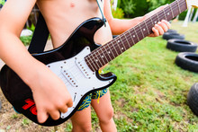 Detail Of An Electric Guitar, Held By A Child In His Backyard On His Summer Vacation.