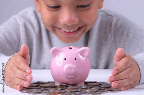 Fotografie, Obraz  Asian boy looking to piggy bank and various coins