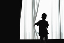 Child Feeling Bored Due To Staying At Home And Restricted From Coronavirus Pandemic. School Closing Has A Negative Impact On Children's Mental Health. Silhouette Of A Kid Opening Curtain Window.