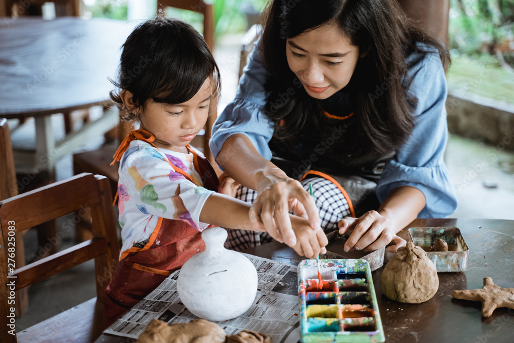 Fototapety, obrazy: daughter learning about painting color with the guidance of his mother