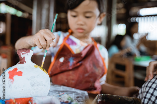 Fotografija daughter learning about painting color in pottery workshop