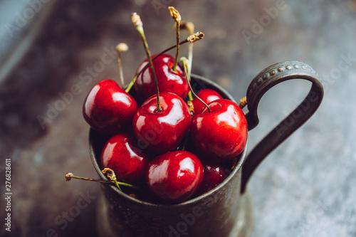 Fotografía  Ripe and juicy cherries in old metal cup on the dark rustic background