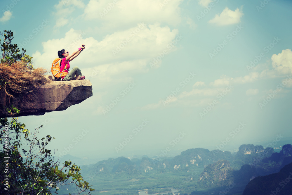 Fototapety, obrazy: Successful woman hiker taking picture with smartphone at cliff edge on mountain top