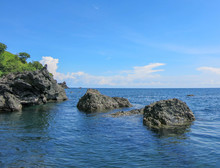 Rocky Cliffs Of Abstract Shapes Protrude Above The Surface. Crystal Clear Sea Water. Azure Blue Sea And Sky With Partial Cloud Cover. Tropical Vegetation. Lava Stones And Rocks.