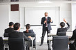 Business Audience raising hand up while businessman is speaking in training for Opinion with Meeting Leader in Conference Room