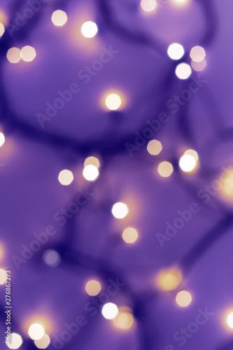 Golden festive bokeh lights on blurred violet background. Christmas or party concept
