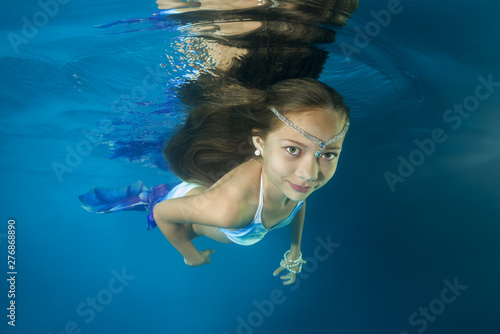 Fotografija  A girl in a mermaid costume poses underwater in a pool